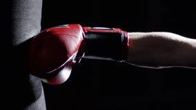 Μαχητής που ασκεί μερικά λακτίσματα με Punching την τσάντα - ένα άτομο με μια δερματοστιξία που εγκιβωτίζει στο σκοτεινό υπόβαθρο στοκ εικόνα