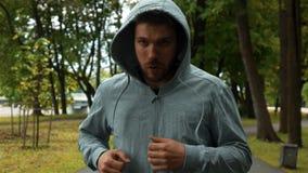 Μαχητής που τρέχει στο πάρκο και brandish τα χέρια όπως τον εγκιβωτισμό φιλμ μικρού μήκους