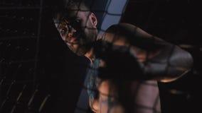 Μαχητής MMA στο κλουβί οκταγώνων τα όμορφα μάτια φωτογραφικών μηχανών τέχνης διαμορφώνουν την πλήρη γοητεία που τα πράσινα βασικά φιλμ μικρού μήκους