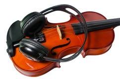 Μαύρα ακουστικά σε ένα κλασσικό ξύλινο βιολί στοκ εικόνα με δικαίωμα ελεύθερης χρήσης