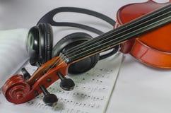 Μαύρα ακουστικά σε ένα κλασσικό ξύλινο βιολί στοκ εικόνες με δικαίωμα ελεύθερης χρήσης