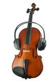Μαύρα ακουστικά σε ένα κλασσικό ξύλινο βιολί στοκ εικόνες