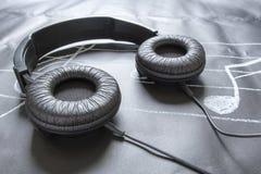 Μαύρα ακουστικά στη μαύρη σημείωση μουσικής Στοκ εικόνες με δικαίωμα ελεύθερης χρήσης