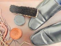 Μαύρα λαμπρά παπούτσια με τη στιλβωτική ουσία παπουτσιών, μια βούρτσα και τα κορδόνια Στοκ Φωτογραφίες