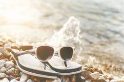 Μαύρα αντανακλημένα γυαλιά ηλίου πέτρες Σκιά από τα γυαλιά Φως του ήλιου καλοκαίρι θαλασσινών κοχυλιών άμμου πλαισίων έννοιας ανα Στοκ Φωτογραφία