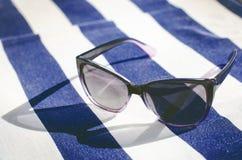 Μαύρα αντανακλημένα γυαλιά ηλίου σε ένα κάλυμμα Σκιά από τα γυαλιά Φως του ήλιου καλοκαίρι θαλασσινών κοχυλιών άμμου πλαισίων ένν Στοκ Εικόνες