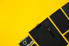 Μαύρα αντικείμενα από το γραφείο σε ένα κίτρινο υπόβαθρο Εργασία και δημιουργικότητα Τοπ όψη Στοκ Εικόνες