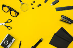 Μαύρα αντικείμενα από το γραφείο σε ένα κίτρινο υπόβαθρο Εργασία και δημιουργικότητα Τοπ όψη Στοκ Φωτογραφία