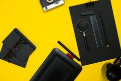 Μαύρα αντικείμενα από το γραφείο σε ένα κίτρινο υπόβαθρο Εργασία και δημιουργικότητα Τοπ όψη Στοκ εικόνες με δικαίωμα ελεύθερης χρήσης