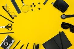 Μαύρα αντικείμενα από το γραφείο σε ένα κίτρινο υπόβαθρο Εργασία και δημιουργικότητα Τοπ όψη Στοκ Φωτογραφίες