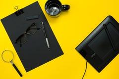 Μαύρα αντικείμενα από το γραφείο σε ένα κίτρινο υπόβαθρο Εργασία και δημιουργικότητα Τοπ όψη Στοκ φωτογραφία με δικαίωμα ελεύθερης χρήσης
