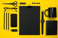 Μαύρα αντικείμενα από το γραφείο σε ένα κίτρινο υπόβαθρο Εργασία και δημιουργικότητα Τοπ όψη Στοκ Εικόνα