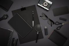 Μαύρα αντικείμενα από το γραφείο σε ένα σκούρο γκρι υπόβαθρο Απασχοληθείτε Στοκ φωτογραφίες με δικαίωμα ελεύθερης χρήσης