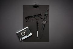 Μαύρα αντικείμενα από το γραφείο σε ένα σκούρο γκρι υπόβαθρο Απασχοληθείτε Στοκ Φωτογραφίες