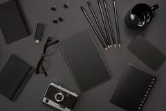 Μαύρα αντικείμενα από το γραφείο σε ένα σκούρο γκρι υπόβαθρο Εργασία και δημιουργικότητα Τοπ όψη Στοκ Εικόνα