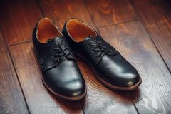 Μαύρα αρσενικά παπούτσια δέρματος στο ξύλινο υπόβαθρο Στοκ εικόνα με δικαίωμα ελεύθερης χρήσης