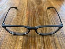Μαύρα γυαλιά στο επιτραπέζιο υπόβαθρο στοκ εικόνες