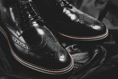 Μαύρα γυαλισμένα η Οξφόρδη παπούτσια στο μαύρο υπόβαθρο Στοκ φωτογραφίες με δικαίωμα ελεύθερης χρήσης