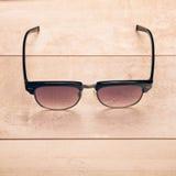 Μαύρα γυαλιά ηλίου στο ξύλινο πάτωμα Στοκ Εικόνες