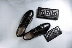 Μαύρα διατρυπημένα oxfords παπουτσιών, ένα πορτοφόλι και μια τηλεφωνική περίπτωση σε ένα άσπρο υπόβαθρο εγγράφου στοκ φωτογραφία