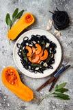 Μαύρα ζυμαρικά με την ψημένη butternut κολοκύνθη, το τυρί παρμεζάνας και την τηγανισμένη φασκομηλιά Μαύρη και πορτοκαλιά έννοια γ Στοκ Φωτογραφίες