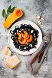 Μαύρα ζυμαρικά με την ψημένη butternut κολοκύνθη, το τυρί παρμεζάνας και την τηγανισμένη φασκομηλιά Μαύρη και πορτοκαλιά έννοια γ Στοκ Εικόνα