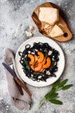 Μαύρα ζυμαρικά με την ψημένη butternut κολοκύνθη, το τυρί παρμεζάνας και την τηγανισμένη φασκομηλιά Μαύρη και πορτοκαλιά έννοια γ Στοκ Εικόνες