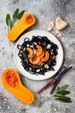 Μαύρα ζυμαρικά με την ψημένη butternut κολοκύνθη, το τυρί παρμεζάνας και την τηγανισμένη φασκομηλιά Μαύρη και πορτοκαλιά έννοια γ Στοκ εικόνα με δικαίωμα ελεύθερης χρήσης