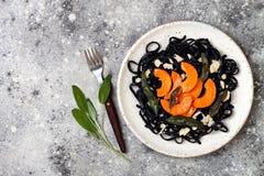 Μαύρα ζυμαρικά με την ψημένη butternut κολοκύνθη, το τυρί παρμεζάνας και την τηγανισμένη φασκομηλιά Μαύρη και πορτοκαλιά έννοια γ Στοκ φωτογραφία με δικαίωμα ελεύθερης χρήσης
