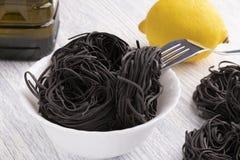 Μαύρα ζυμαρικά σε ένα άσπρο πιάτο σε ένα άσπρο επιτραπέζιο υπόβαθρο στοκ φωτογραφίες