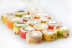 μαύρα καθορισμένα καλυμμένα σούσια Ρόλοι με το σολομό και τα λαχανικά, chopstick Στοκ Φωτογραφίες