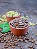 Μαύρα και πράσινα σιτάρια καφέ στα φλυτζάνια με το φύλλο εν πλω Στοκ εικόνες με δικαίωμα ελεύθερης χρήσης