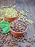 Μαύρα και πράσινα σιτάρια καφέ στα φλυτζάνια με το φύλλο στο σκοτεινό πίνακα Στοκ φωτογραφία με δικαίωμα ελεύθερης χρήσης