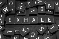 Μαύρα κεραμίδια επιστολών που συλλαβίζουν τη λέξη & x22 exhale& x22  στοκ φωτογραφία