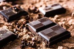 Μαύρα κομμάτια σοκολάτας στη σκόνη σοκολάτας Στοκ φωτογραφία με δικαίωμα ελεύθερης χρήσης