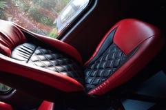 Μαύρα κόκκινα καθίσματα δέρματος στο αυτοκίνητο στοκ φωτογραφία