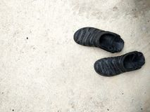 Μαύρα λαστιχένια σανδάλια στο άσπρο συγκεκριμένο υπόβαθρο με τη σκιά Μαύρα λαστιχένια σανδάλια που απομονώνονται στη λευκιά συγκε στοκ εικόνες με δικαίωμα ελεύθερης χρήσης