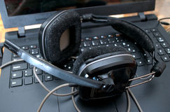 Μαύρα μεγάλα ακουστικά του DJ που αφήνονται στο lap-top μετά από να αναμίξει τη μουσική Στοκ εικόνα με δικαίωμα ελεύθερης χρήσης