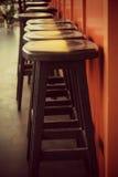 Μαύρα ξύλινα σκαμνιά σε έναν κόκκινο καφέ Στοκ Φωτογραφία