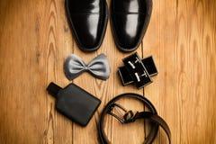 Μαύρα παπούτσια, ένας γκρίζος δεσμός τόξων και μανικετόκουμπα πουκάμισων στοκ εικόνες
