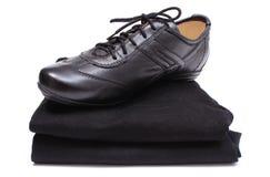 Μαύρα παπούτσια στο σωρό των γυναικείων ενδυμάτων Άσπρη ανασκόπηση Στοκ εικόνες με δικαίωμα ελεύθερης χρήσης