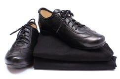 Μαύρα παπούτσια στο σωρό των γυναικείων ενδυμάτων Άσπρη ανασκόπηση Στοκ εικόνα με δικαίωμα ελεύθερης χρήσης