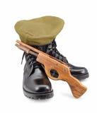 Μαύρα παπούτσια στρατού, Beret, πυροβόλο όπλο στα άσπρα υπόβαθρα Στοκ Εικόνα