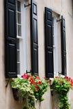 Μαύρα παραθυρόφυλλα σε ένα κτήριο κρέμας με τα ρέοντας κιβώτια καλλιεργητών στο Τσάρλεστον, νότια Καρολίνα Στοκ φωτογραφία με δικαίωμα ελεύθερης χρήσης