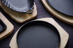 Μαύρα πιάτα χυτοσιδήρου για την εξυπηρέτηση, στις ξύλινες στάσεις Στοκ Φωτογραφία