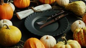 Μαύρα πιάτο και μαχαιροπήρουνα που περιβάλλονται από τις κολοκύθες απόθεμα βίντεο
