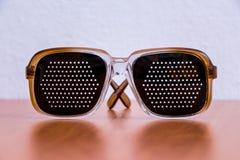 Μαύρα πλαστικά γυαλιά σε έναν καφετή πίνακα στοκ φωτογραφία με δικαίωμα ελεύθερης χρήσης
