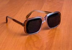 Μαύρα πλαστικά γυαλιά σε έναν καφετή πίνακα στοκ εικόνες