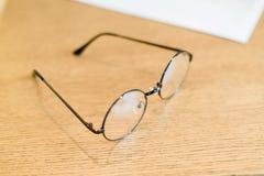 Μαύρα πλαστικά γυαλιά κύκλων στον ελάχιστο ξύλινο πίνακα επιδέσμου Στοκ εικόνα με δικαίωμα ελεύθερης χρήσης