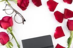 Μαύρα σημειωματάριο και γυαλιά που διακοσμούνται με τα κόκκινα τριαντάφυλλα Στοκ Φωτογραφίες